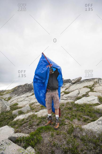 Mountaineer taking shelter in tarp bag, Chilliwack, British Columbia, Canada