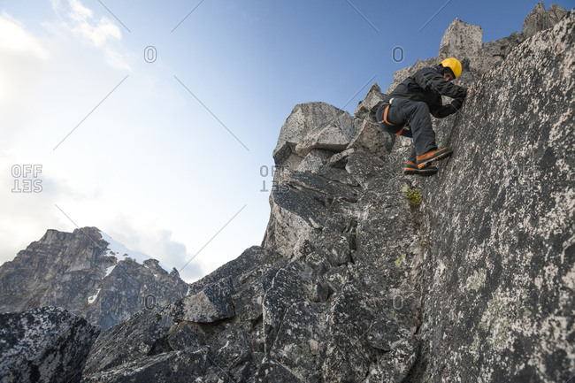 Mountain climber climbing down rocky cliff in North Cascade Mountain Range, Chilliwack, British Columbia, Canada