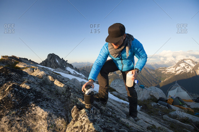 Mountain climber melting snow to make water with stove, Chilliwack, British Columbia, Canada