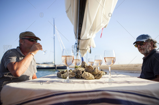 Two men having oyster and wine tasting onboard sailboat, Banc d'Arguin, Arcachon Bay, France