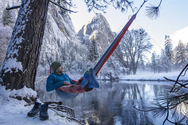 Man resting in hammock on lakeshore during winter hiking, High Sierras, California, USA