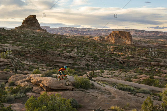 Man cycling in mountains during sunset, Moab, Utah, USA