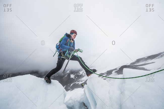 Woman crossing crevasse on Coleman Glacier on Mount Baker, Washington State, USA