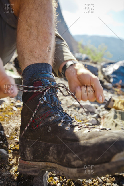 A mountaineer ties his bootlace.