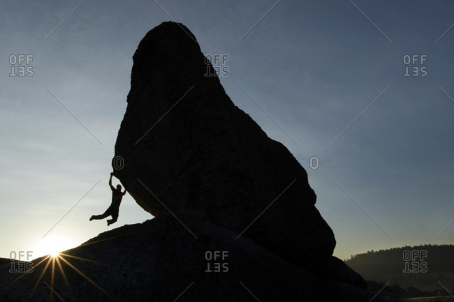 Climber climbing on boulder at in Valley of Frogs near Creel, Chihuahua, Mexico