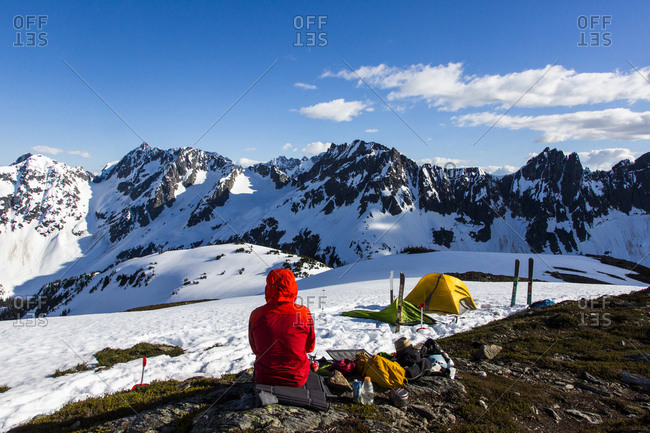Man camping in snowy mountains at Sahale Arm of Sahale Peak, North Cascades National Park, Washington State, USA