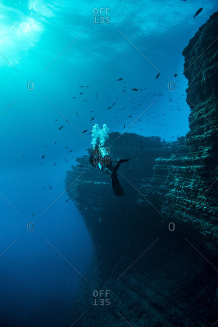 Scuba diver swimming next to rocky wall of El boiler, Revillagigedo Islands, Colima, Mexico