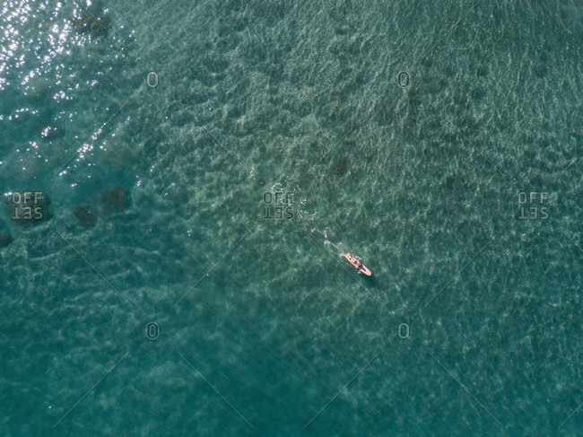 Aerial view of young woman surfing in crystal clear water, Tenerife, Canary Islands, Spain