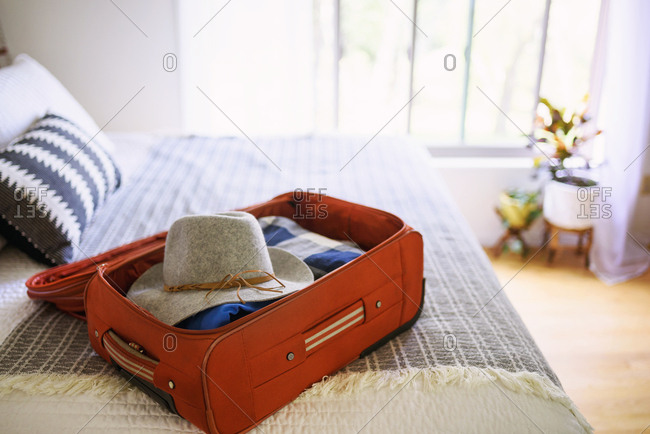 A packed suitcase sitting open on a bed