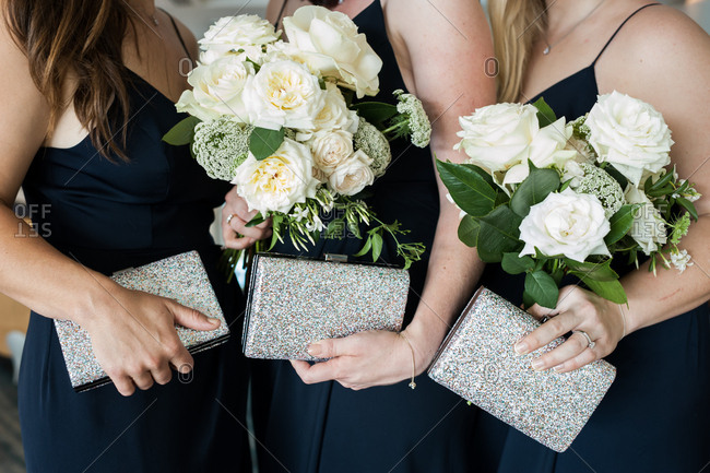 Bridesmaids holding bouquets and sparkly clutches