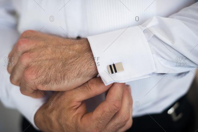 Man putting cufflink on white shirt
