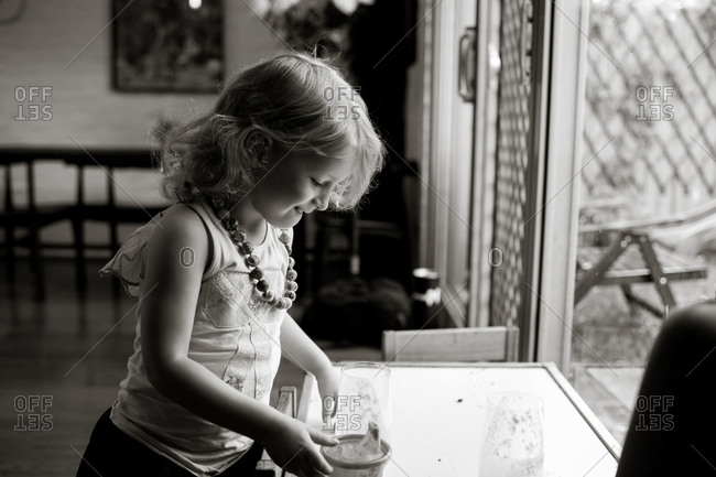 Child looking into a glass cup in black and white