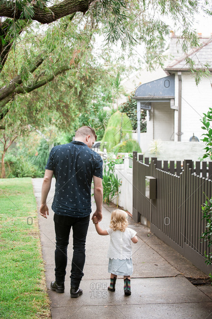 Rear view of father walking down sidewalk with toddler daughter
