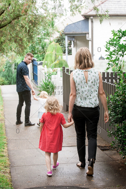 Rear view of family walking down sidewalk together