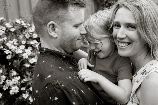 Parents holding little girl in black and white