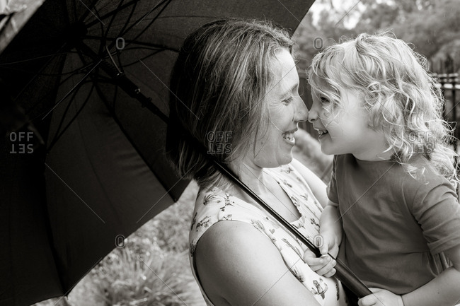 Mother giving toddler girl Eskimo kisses in black and white