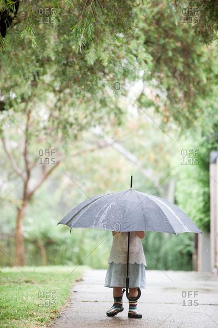 Little girl standing on sidewalk holding umbrella