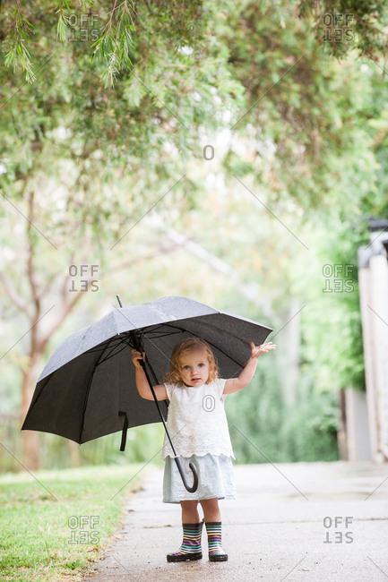 Toddler girl standing on sidewalk holding umbrella