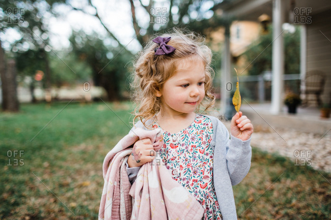 Little blond girl looking at a leaf in autumn