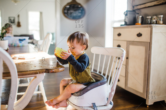 Messy toddler boy eating lunch in a booster seat stock photo - OFFSET