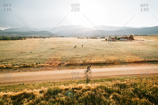Boulder, Colorado - August 1, 2017: Man cycling on dirt road toward mountains at sunset