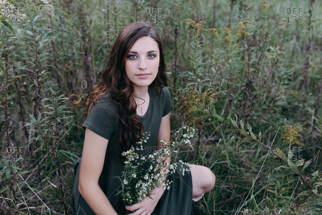 Portrait of a young brunette woman holding wildflowers