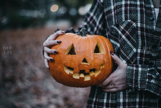 Young woman holding scary carved pumpkin for Halloween