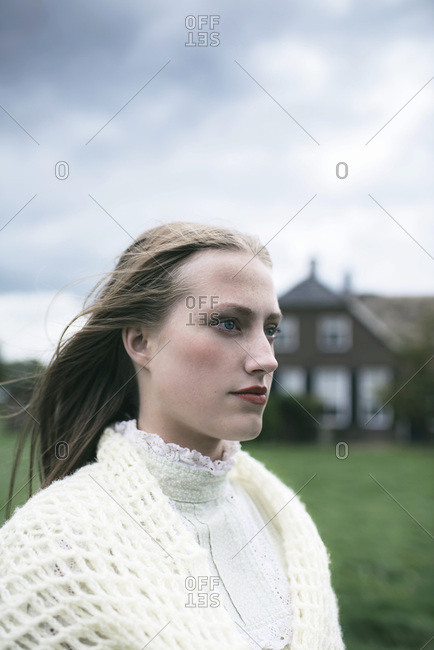 Woman in white clothes at farm under stormy sky