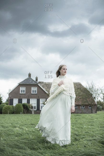 Woman in white dress in rural landscape with cloudy sky