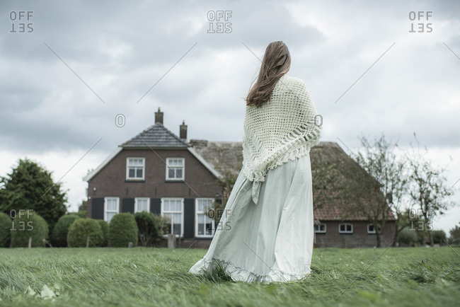 Woman in white dress in countryside farm with cloudy sky