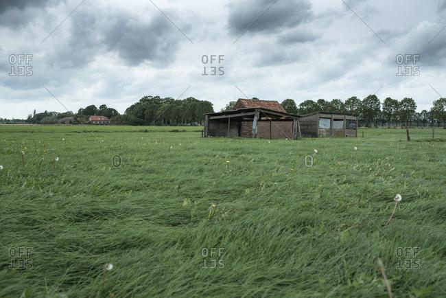 Old shed in rural landscape under dark stormy sky