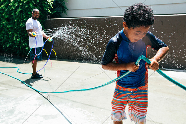 Son crimping hose while dad sprays him with water