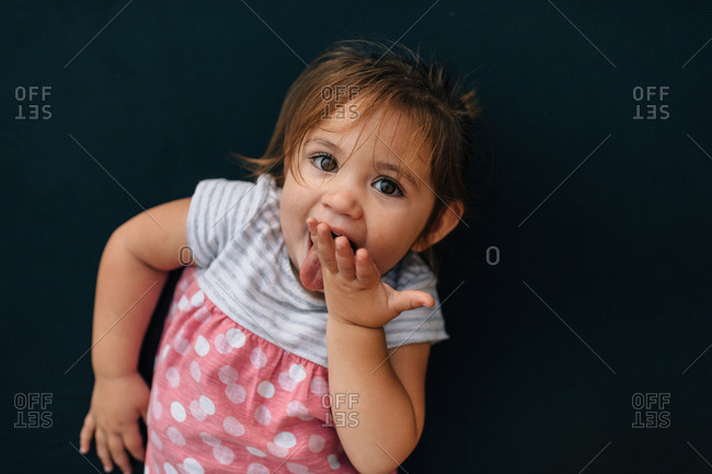 Cute young girl licking her hand
