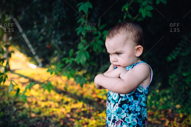 A moody toddler standing in nature