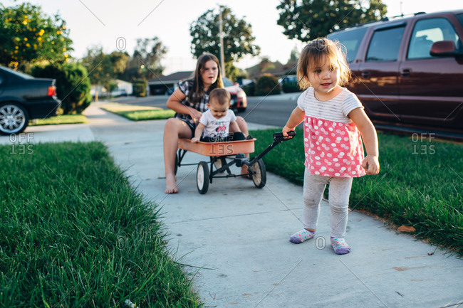 Little girl pulling sisters in a wagon