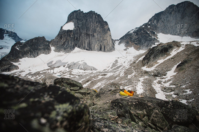 Two campers sleeping in a rocky snow covered mountain landscape