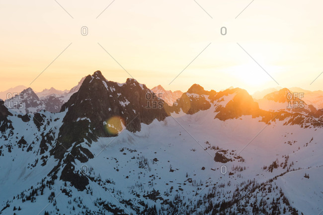 Bright sun seen from behind snow covered mountains