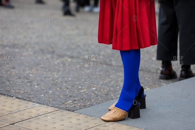 London, England - October 2, 2017: Woman wearing a red skirt with blue tights and tan shoes