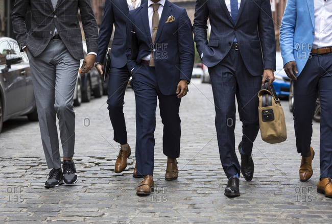 Group of men in stylish suits walking down street