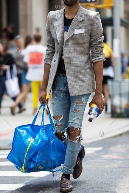 New York City, New York - October 2, 2017: Man wearing ripped jeans and blazer walking down NYC street
