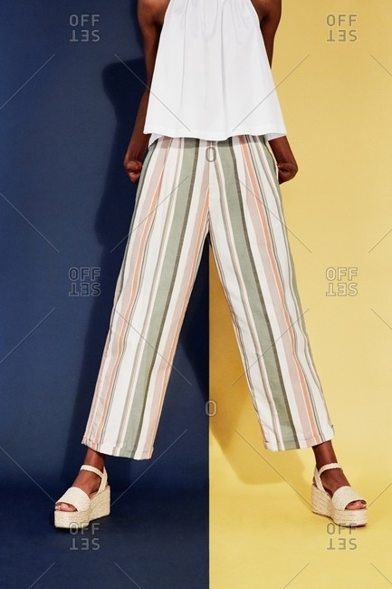 Los Angeles, California - October 2, 2017: Model wearing striped pants on two-tone background