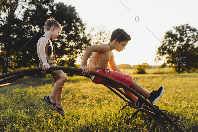 Shirtless brothers playing on metal structure at field during sunset