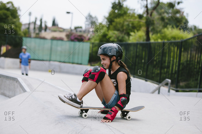 Side view of playful girl sitting on skateboard at sports ramp