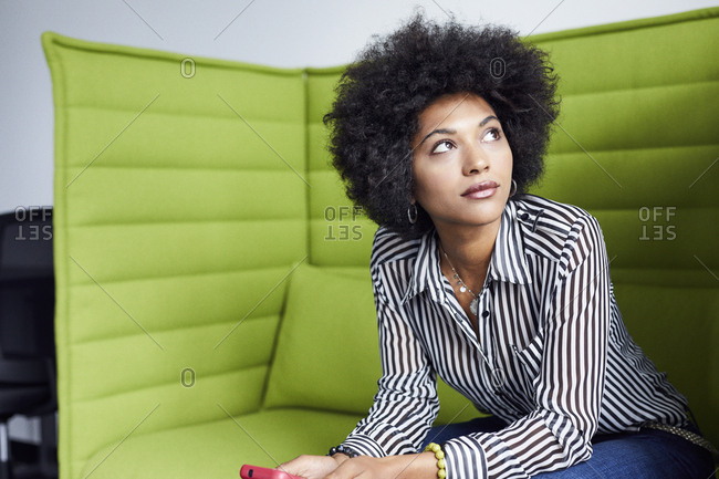 Businesswoman looking away while sitting on sofa in office