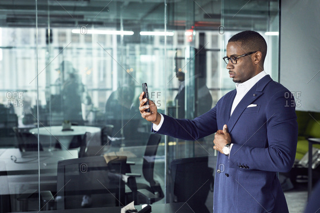 Businessman looking at smart phone while standing in office