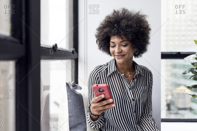 Happy businesswoman using smart phone against window in office