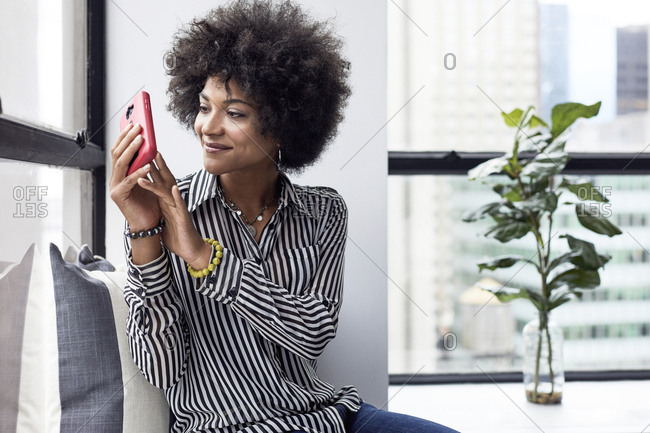 Businesswoman photographing with smart phone while sitting in office