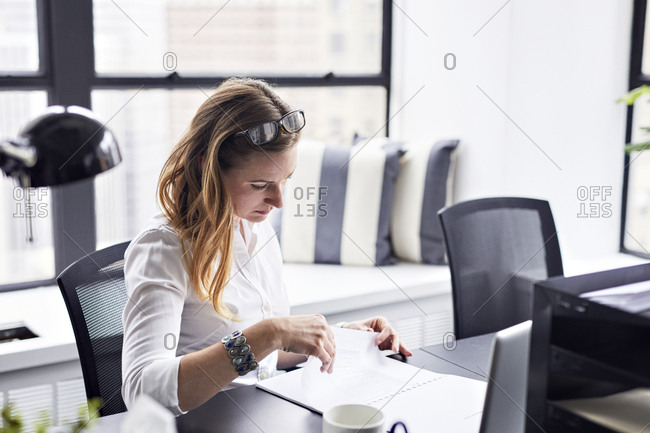 High angle view of businesswoman studying documents in office