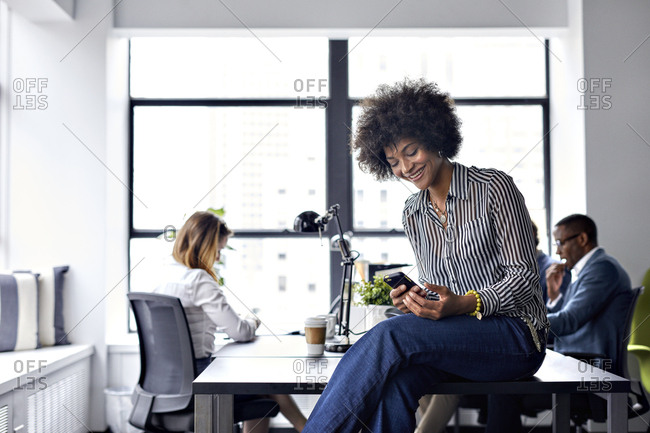Happy businesswoman using smart phone while colleagues working in background