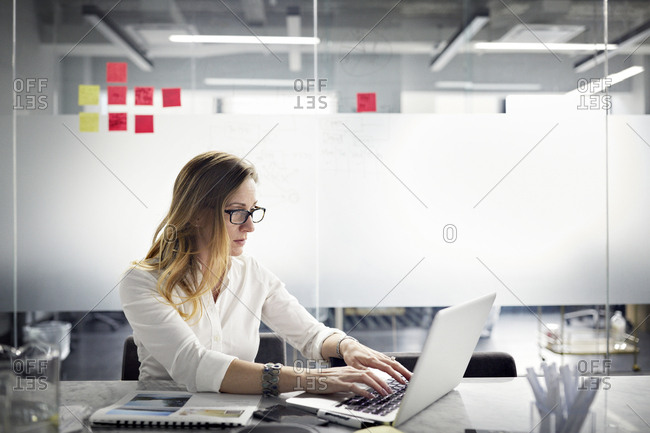 Serious businesswoman using laptop computer while working in office